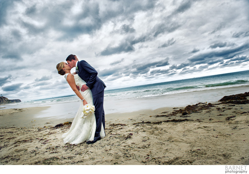 Newlywed kiss under a dramatic sky in Monarch Beach, CA