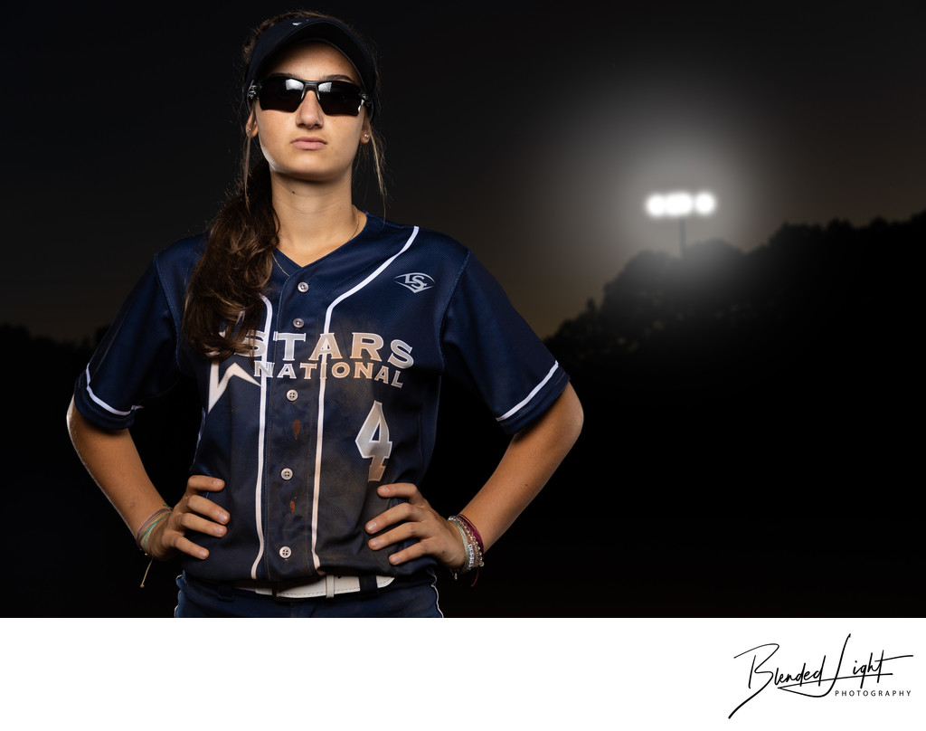 Softball player portrait under the lights on field