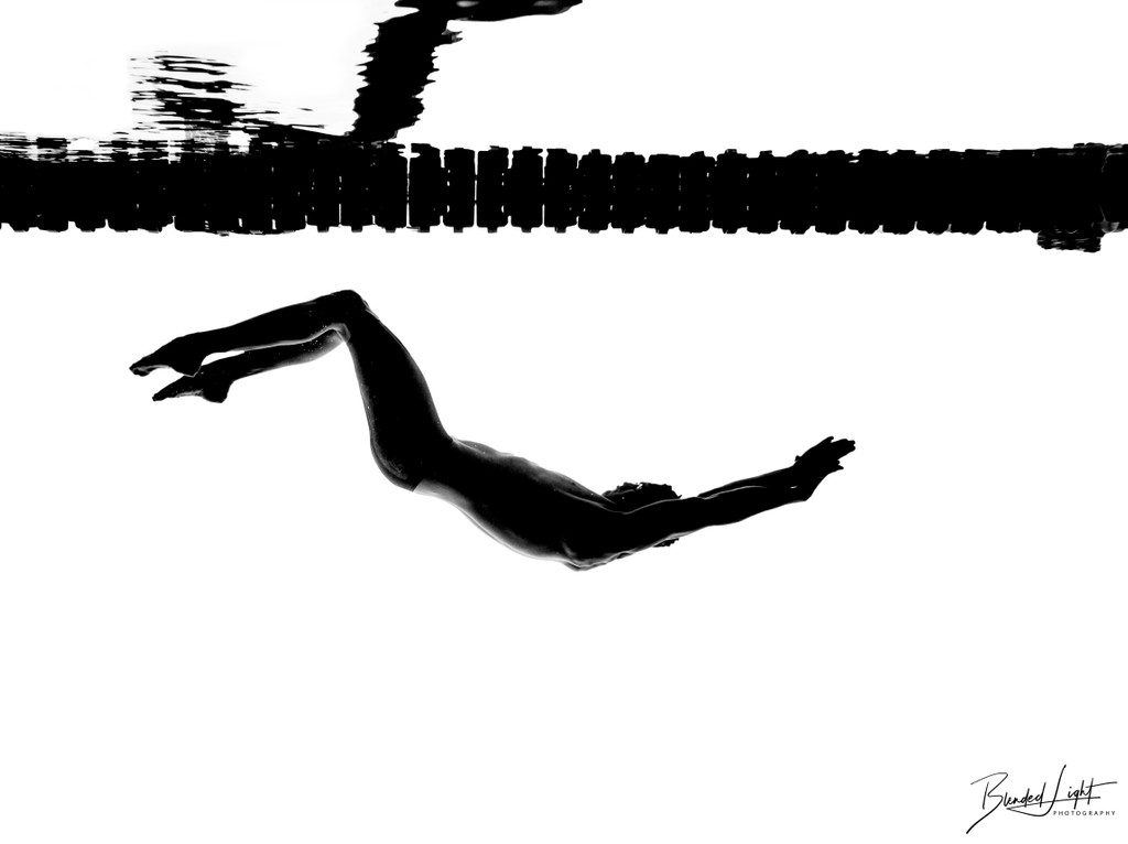 Backstroke silhouette underwater against lane lines