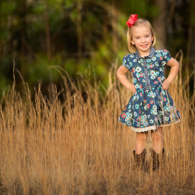 Little girl smiling among the fall grasses portrait
