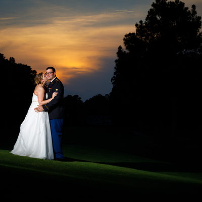 Bride kisses groom picture on the golf course in sunset