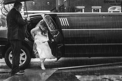 Bride arriving by limo in the rain