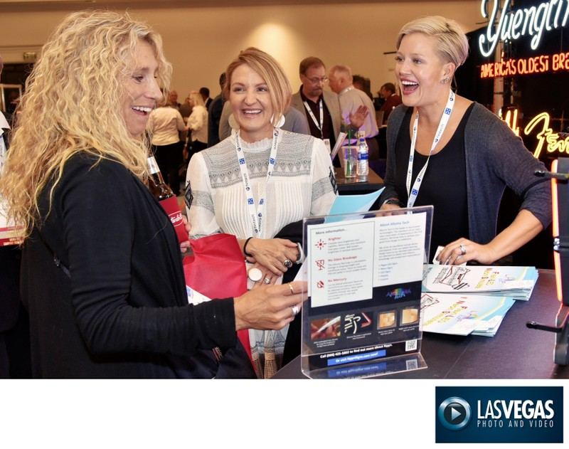 Tradeshow photography of ladies laughing and talking