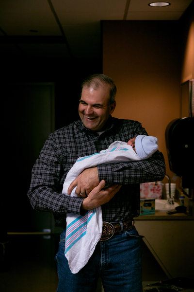 Father Holds Newborn at Home