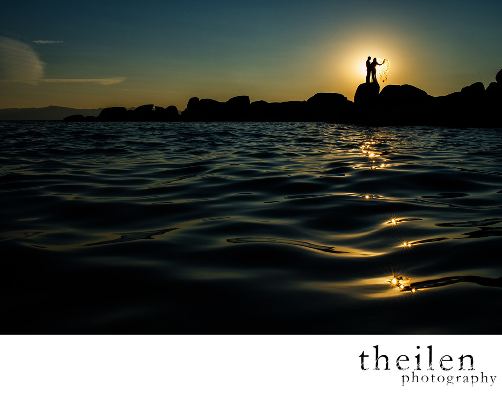 Wedding couple silhouetted at sunset over lake tahoe