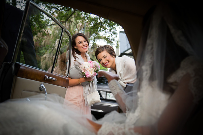 Smiling bridesmaids through Vintage Car