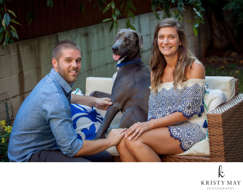 Engaged couple portrait with dog in their backyard