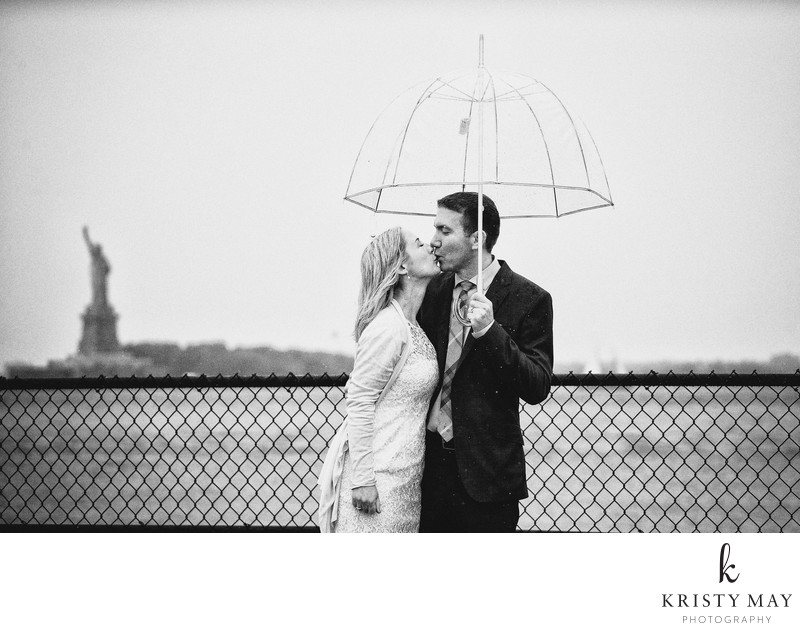 Couple kissing in rain with view of Statue of Liberty