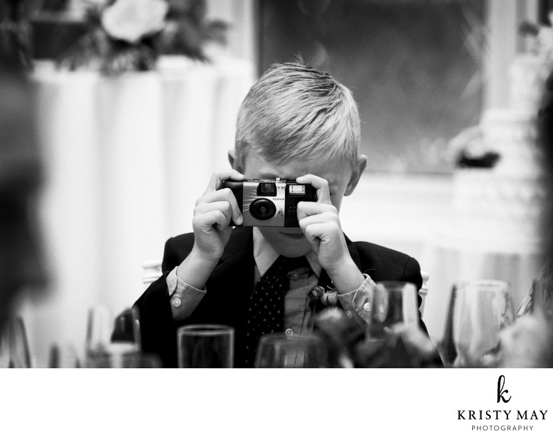 Young boy takes a photo at a wedding with a camera