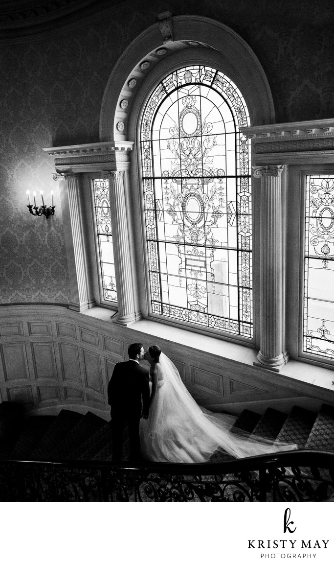 Couple kisses on the stairs at Sleepy Hollow Country Club