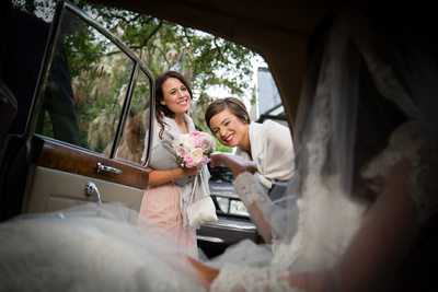 Bridesmaids smile at the Bride in a Vintage Car