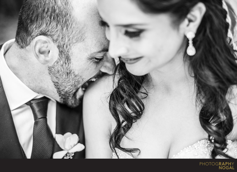 Groom Playfully Biting Bride's Shoulder