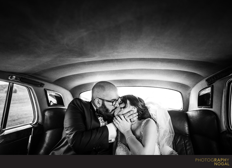 Bride and Groom Kissing in the Back of the Limo