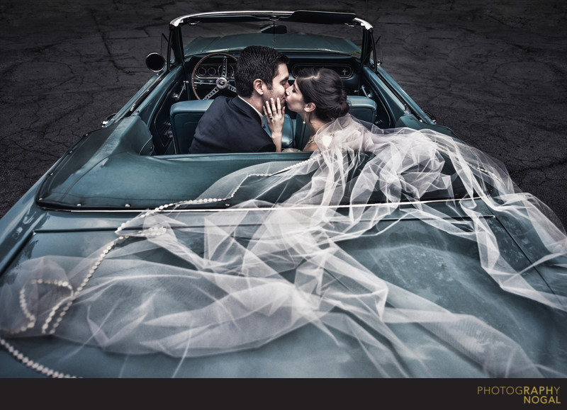 Couple Kissing in a Convertible with Long Veil Flowing