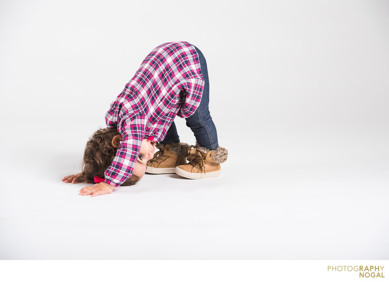 A kid doing the downward dog in the studio