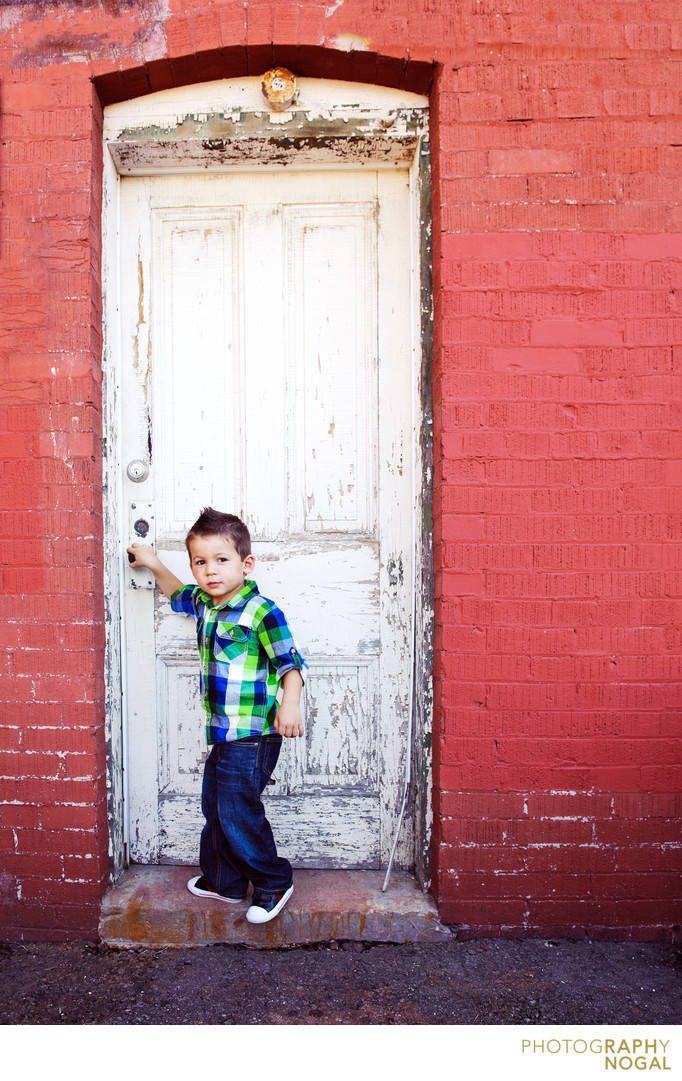boy opening a white rustic door on red building