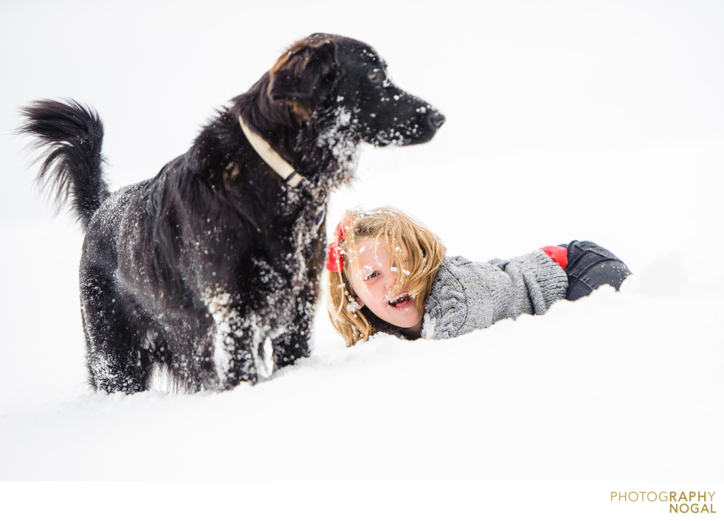 girl playing with dog in the snow