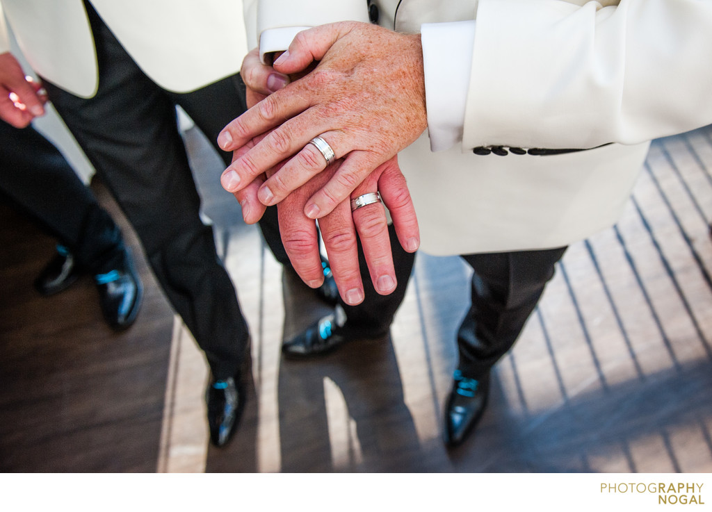 Gay Couple Showing Wedding Rings To Camera