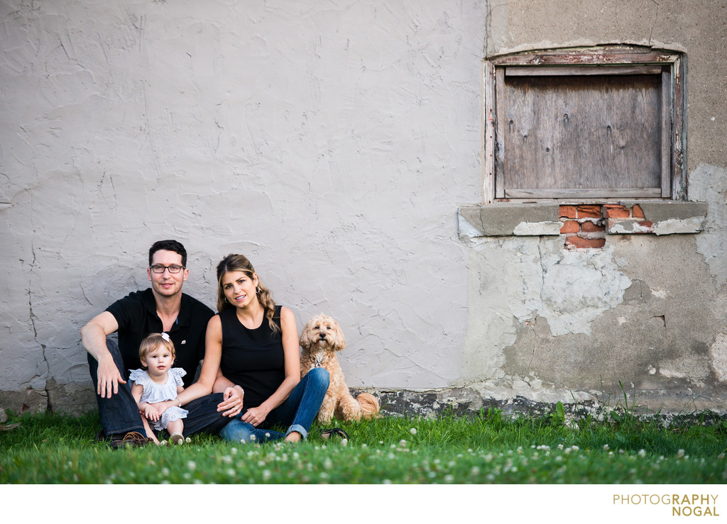 family sitting by rustic wall with baby girl and dog