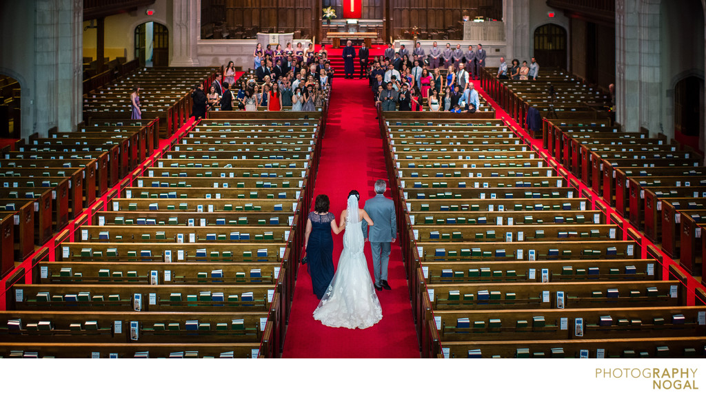 Bride escorted by parents down aisle of grande chruch