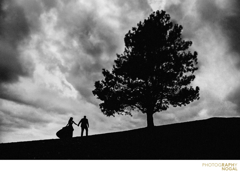 Couple Walking Up Hill Next To A Tree