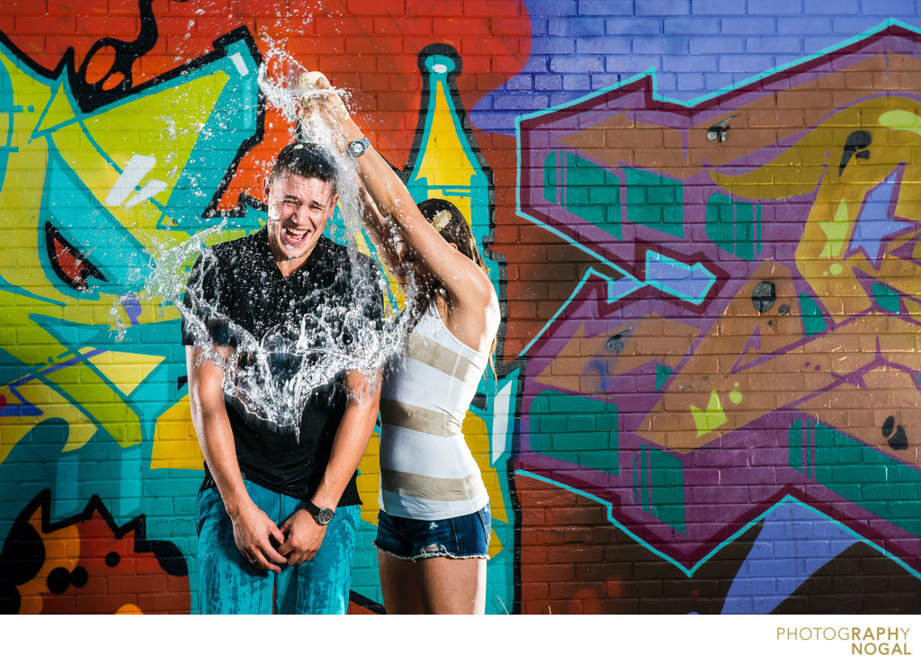 couples splash each other with water during engagement