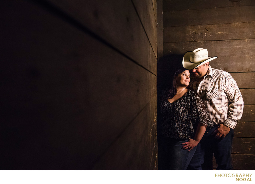 Cowboy couple in a horse stable during engagement shoot