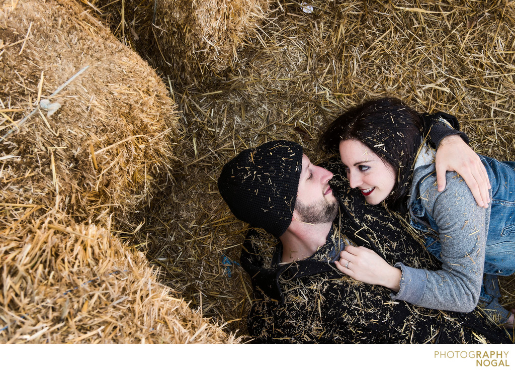 Couple snuggling within the haybale pile
