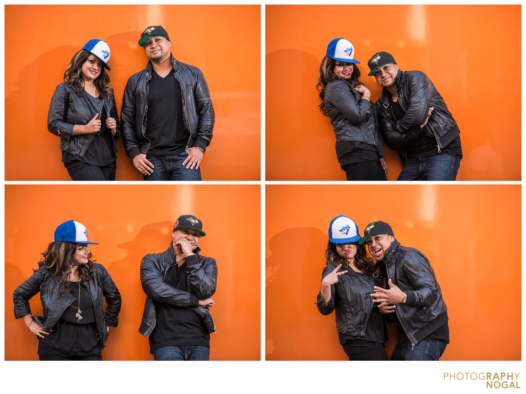 Couple lets loose in sports hats against orange wall