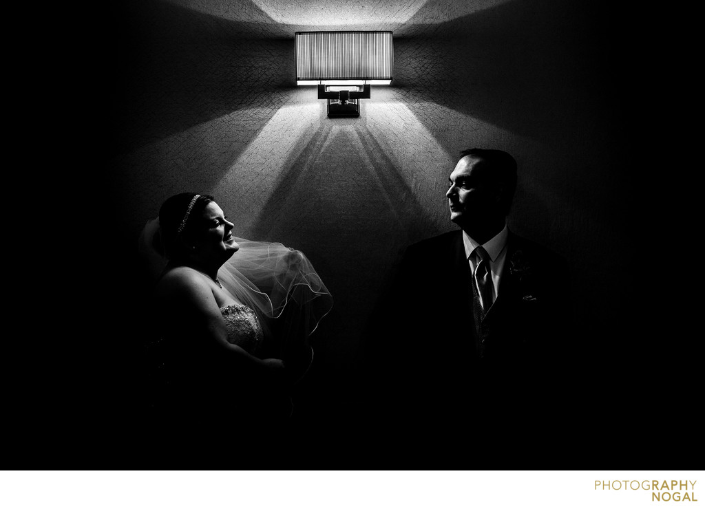 Bride and Groom Next to Light Fixture in Hotel