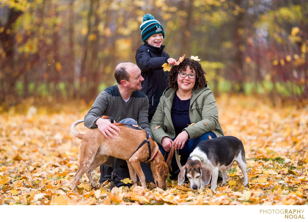 kid putting leaves on mom's head during fall portraits