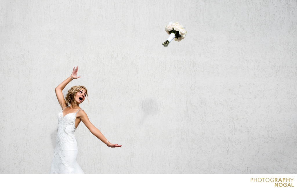 Bride tosses wedding bouquet in front of white wall