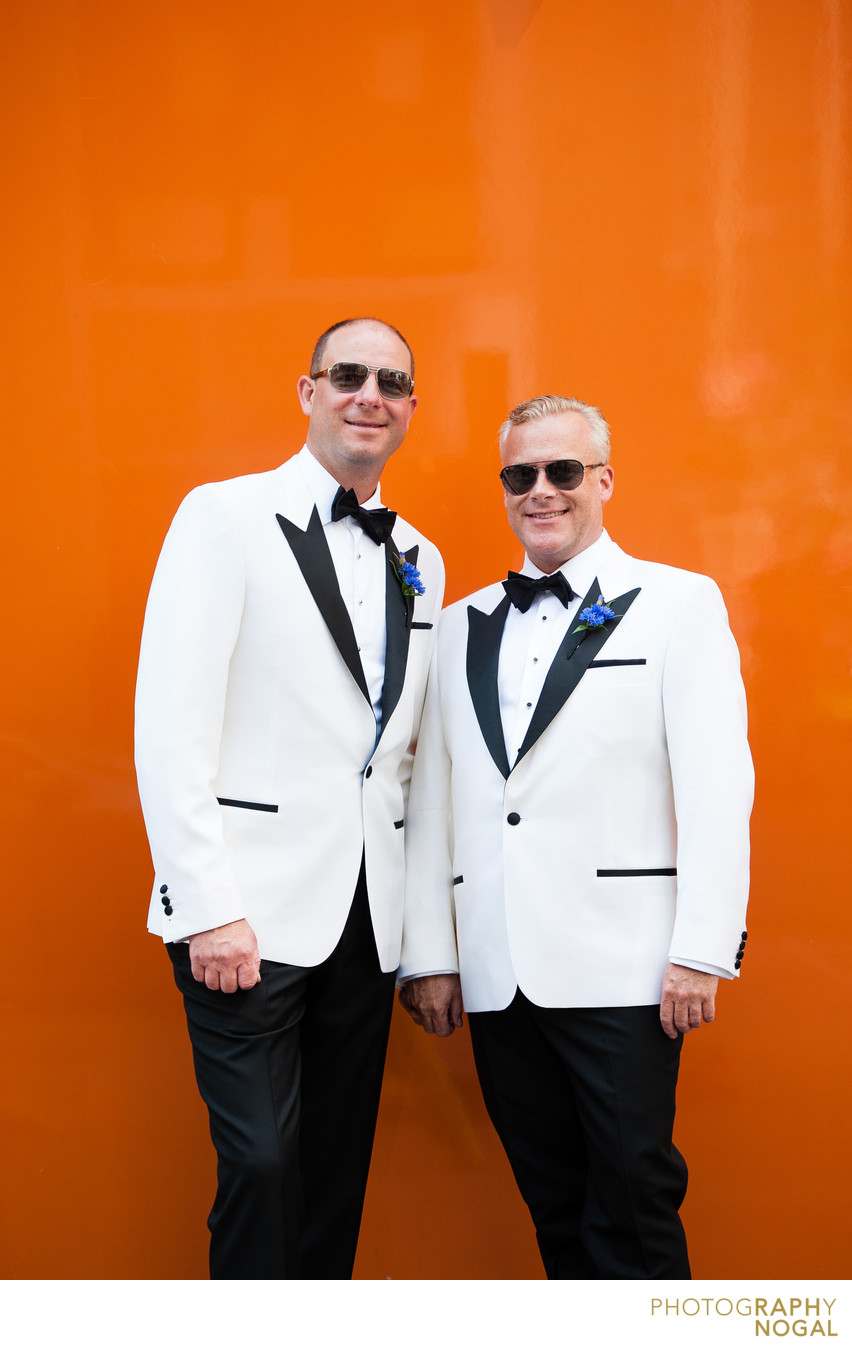 Same Sex Couple Looking Sharp by an Orange Wall
