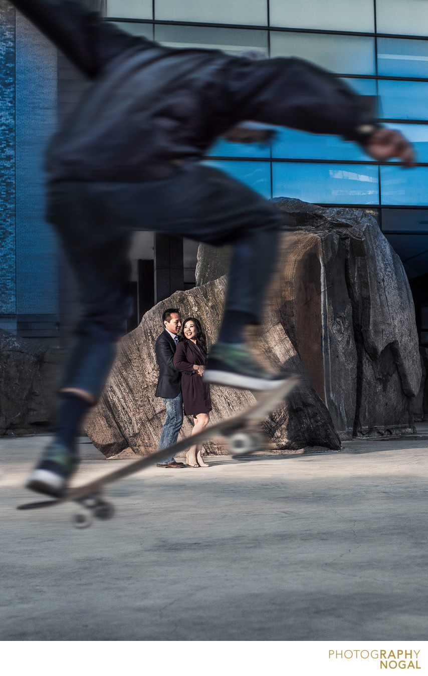 Couple with Skateboarder Jumping to Frame Them.