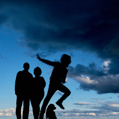 Silhouette of a family and kid jumping