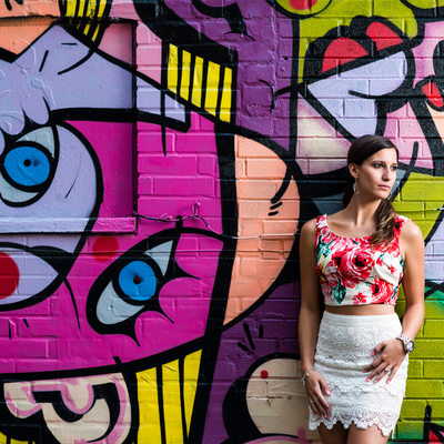Toronto woman in floral top poses against graffiti wall