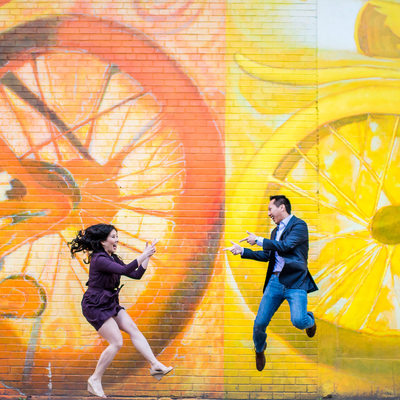 Couple jumping in the air with bike mural behind them