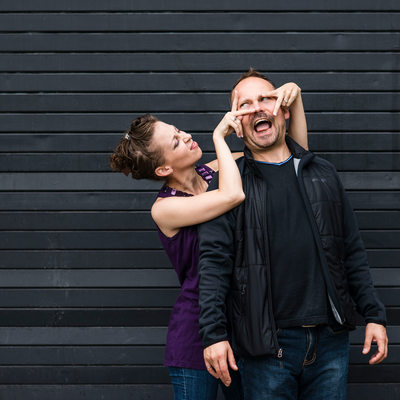 Toronto couple goofs around in front of black backdrop