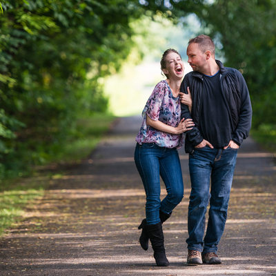 Couple Laughing While Walking In A Park