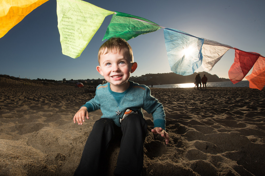 toddler-playing-on-beach-tibetan-prayer-flags