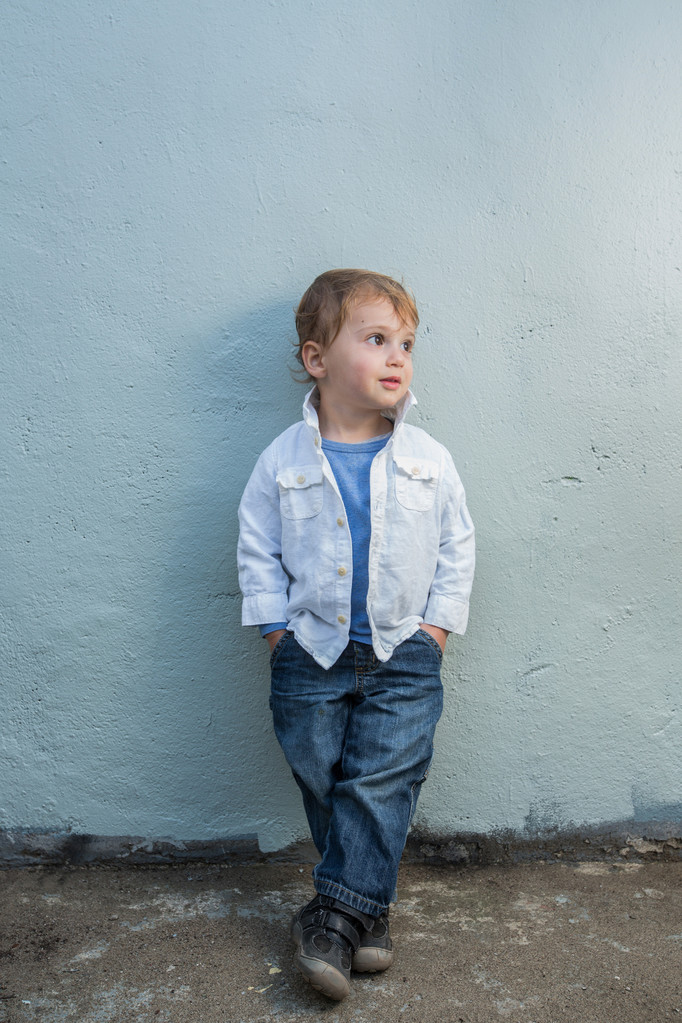 toddler poses in denim and white linen shirt blue wall