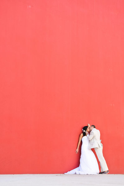 bride groom kissing red wall