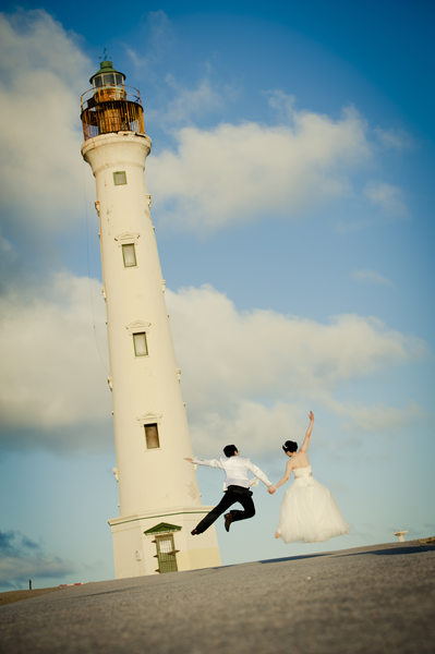 couple jumping lighthouse