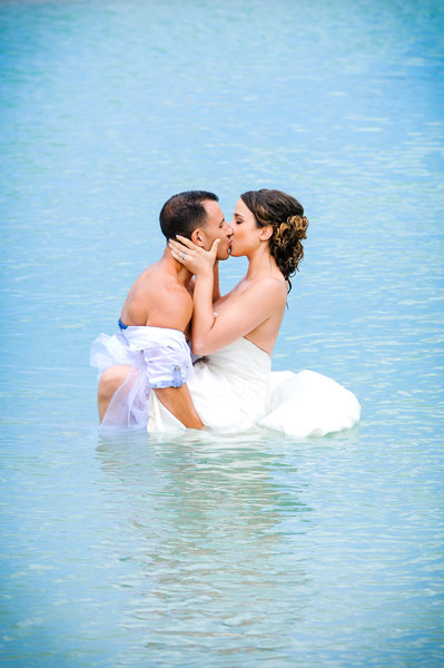 bride and groom kissing in water