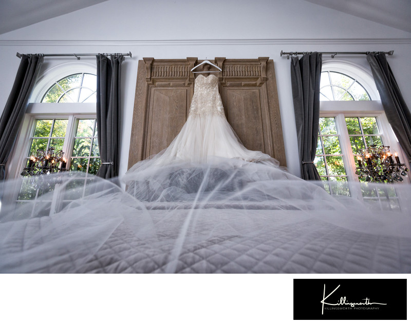 wedding dress hanging above villa aix vineyard bed