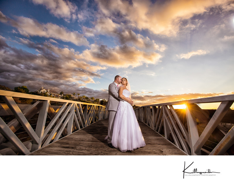 wedding couple loving under sunset and bridge