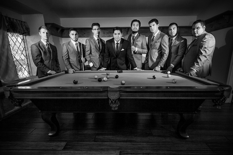 groomsmen posing in front of a pool table
