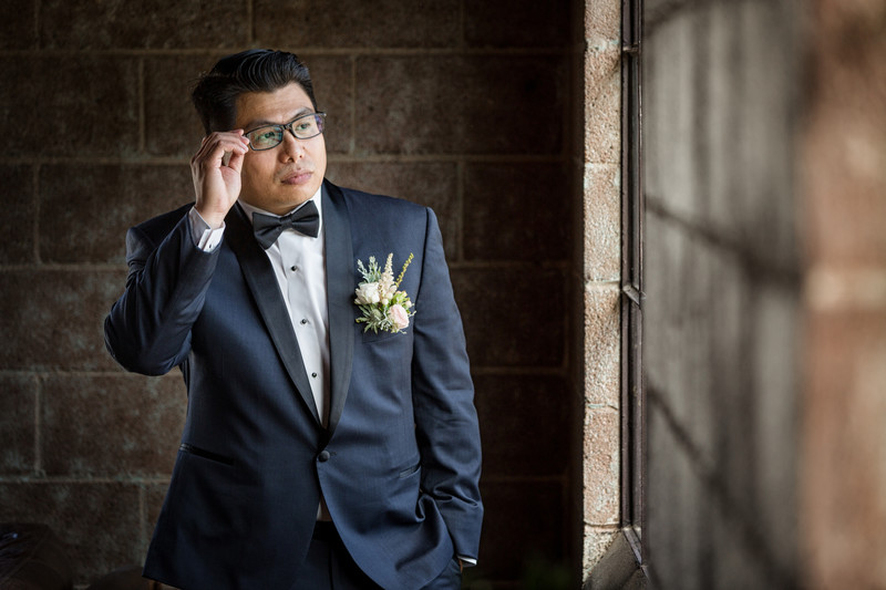 groom with hands on glasses