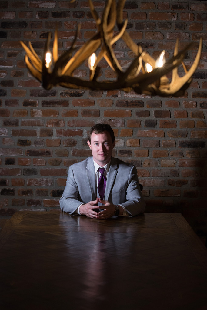 groom sitting at table with antler chandelier