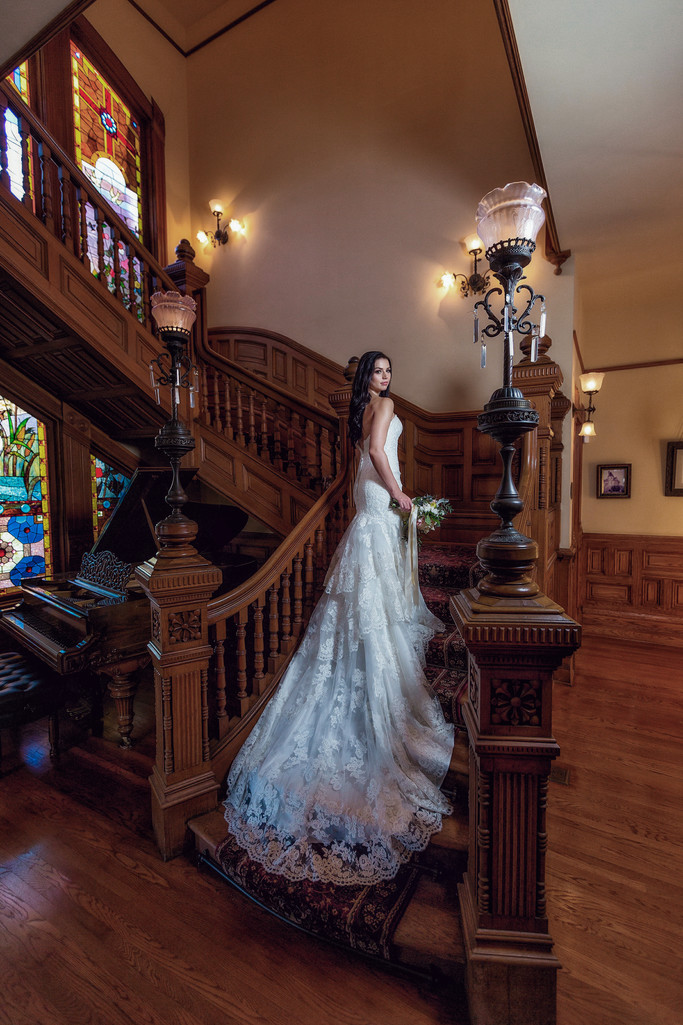 bride posing on the staircase at the Britt Scripps Manor